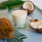 Coconut opened, coconut water and milk flatlay